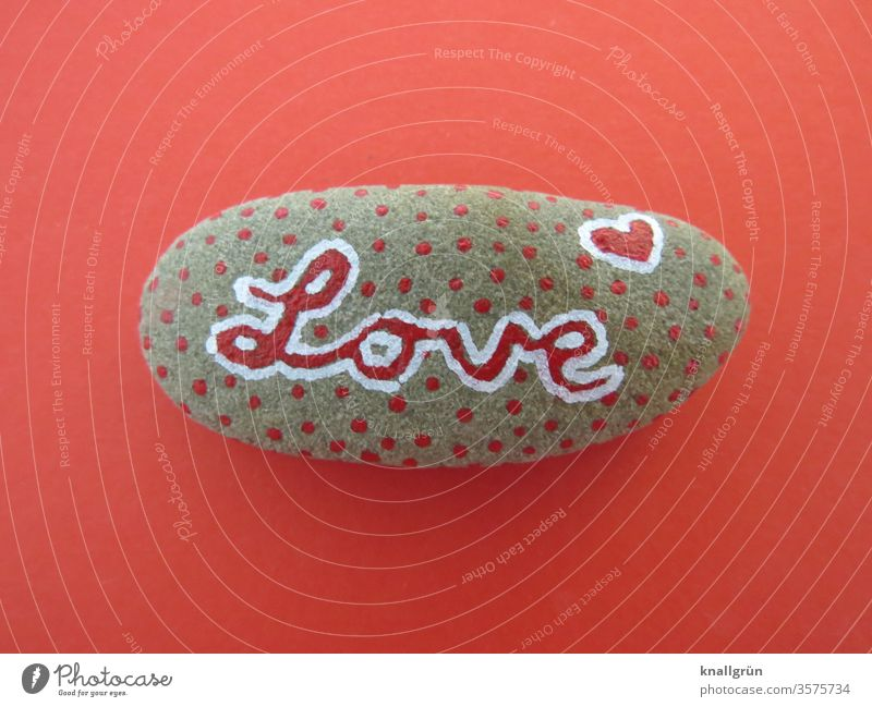 "Red dotted lucky stone with the writing ""Love"" on a red background Lucky Stone Creativity Romance Graffiti Heart Infatuation Emotions Sign Characters"