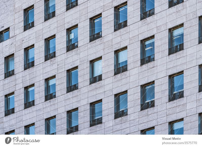 Rows of windows of a business building built in roman travertine marble facade architecture architectural architectonic urban color structure abstract outdoors