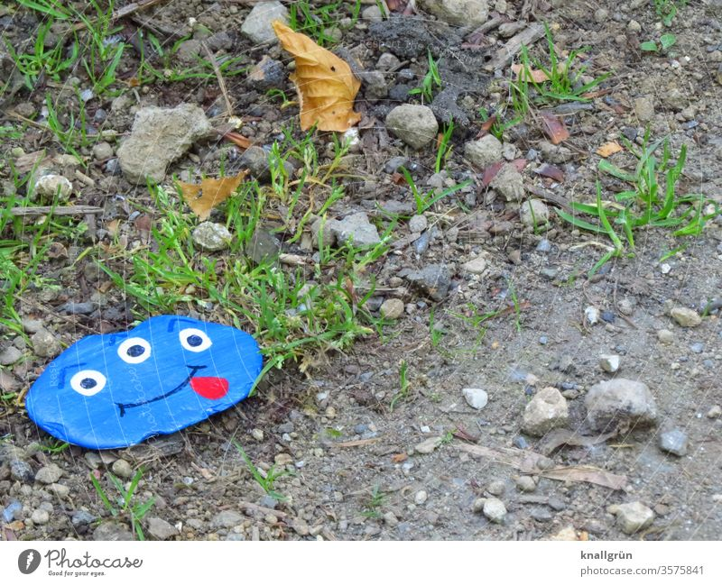 A blue lucky stone with a funny monster face with three eyes and tongue stuck out by the wayside Lucky Stones Monster Joy Wish stone Painted Leisure and hobbies