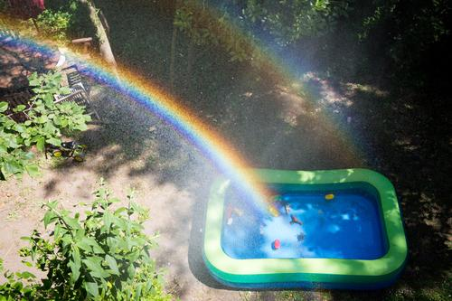 Rainbow over a paddling pool in a garden Garden Paddling pool Water Toys Drops of water spray mist Sunlight Infancy out Beautiful weather warm season Summer