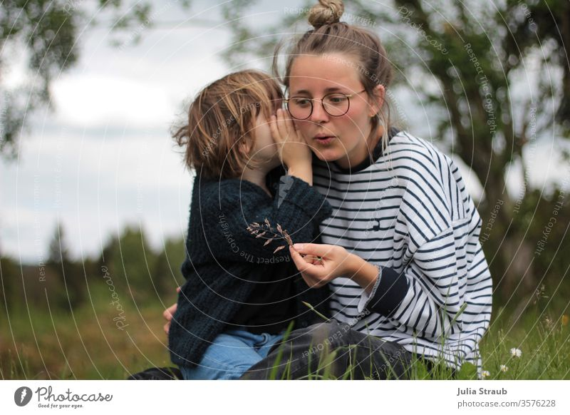 Girl whispers something into the ear of a woman with glasses Listening listen Whisper Meadow flowers Forest Striped Knitted Blue White green Eyeglasses