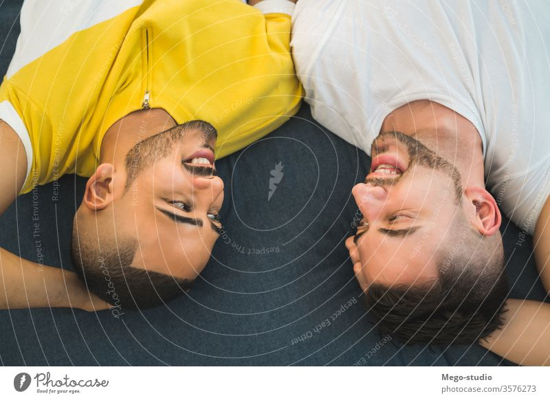Gay couple laying down on the floor. gay love relationship resting date lovely partnership positive relax freedom life young pride dating looking outdoor