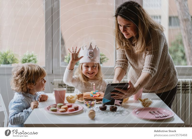 Cheerful little girl making video call on tablet during birthday celebration mother daughter celebrate fun happy remote home distance positive kid mobile phone