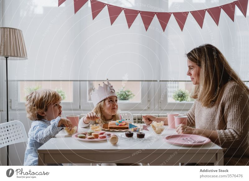 Positive mother playing with kids while having home birthday party children happy celebrate fun parent sibling girl boy together talk positive smile communicate