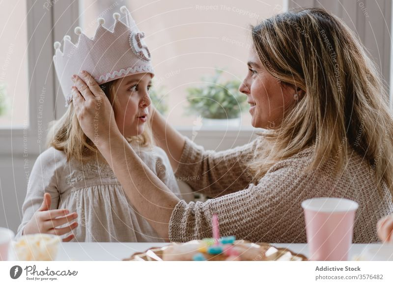 Mother putting decorative  crown on daughter during holiday mother birthday princess love handmade party celebrate home felt kid event fun together girl parent