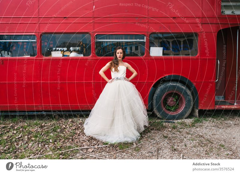 Serious bride standing near red double decker bus newlywed red bus wedding wood wedding dress retro serious unemotional female elegant forest wedding day