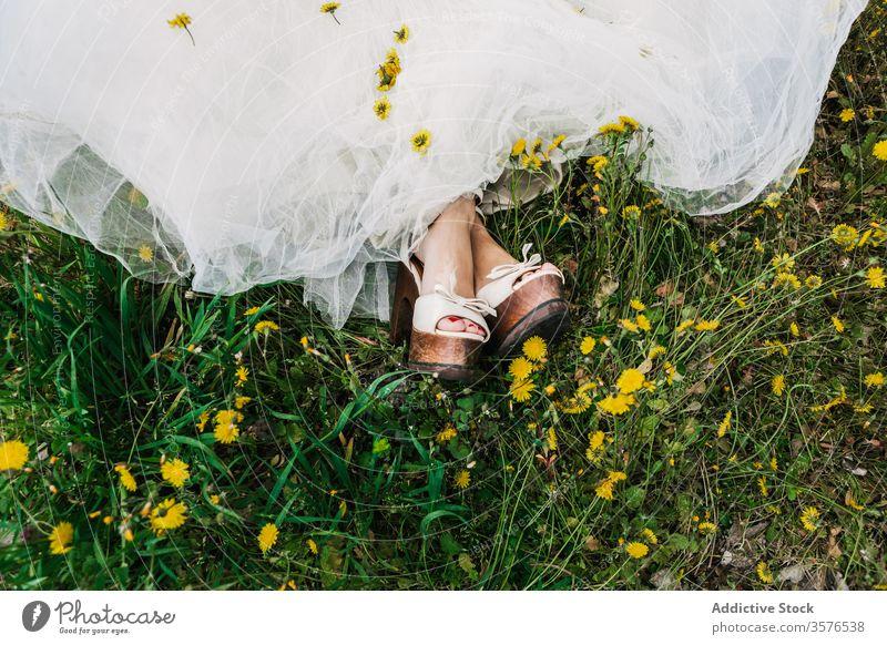 Crop bride in meadow with dandelions newlywed wedding day flower wedding dress high heels bloom female field blossom relax lawn calm tranquil serene sit