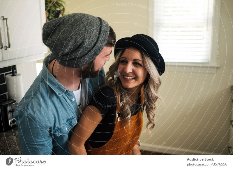 Happy couple embracing standing in the kitchen at home embrace relationship positive hipster style boyfriend affection fondness together love girlfriend partner