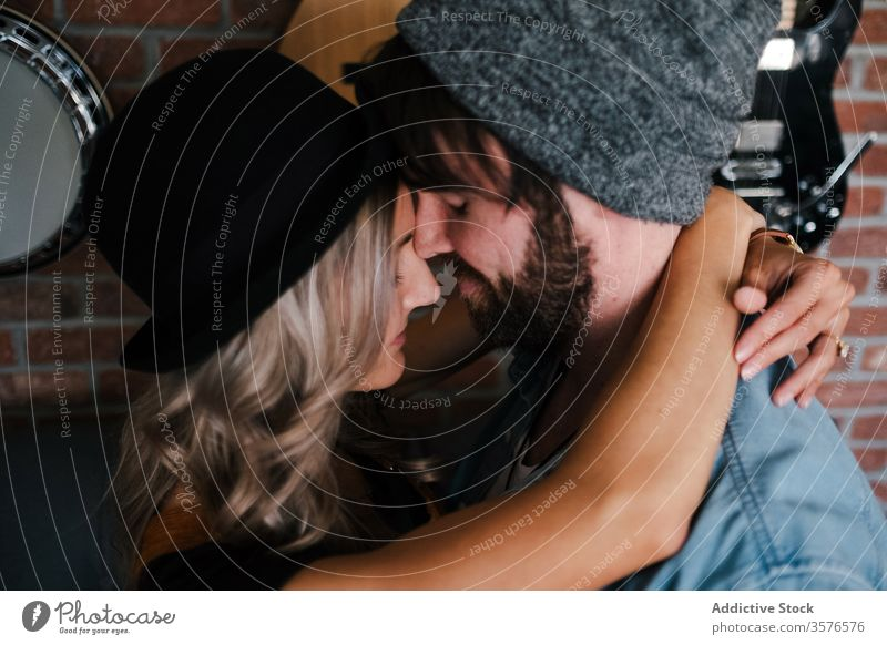 Couple embracing on sofa in apartment couple embrace kiss hipster loft relationship love interior musician boyfriend affection fondness together eyes closed