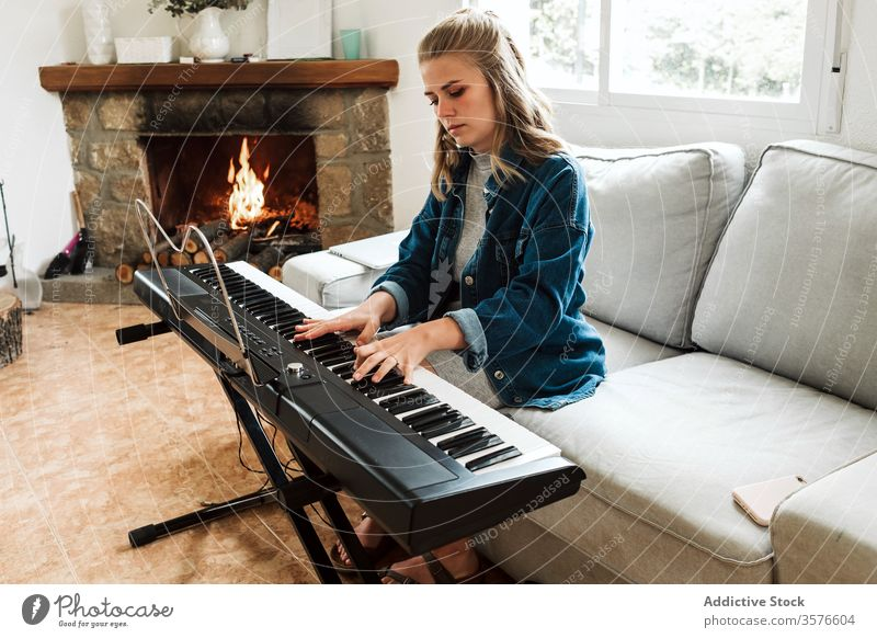 Young woman playing electronic piano at home music young instrument cozy musician electric sofa composer fireplace synthesizer atmosphere relax lifestyle