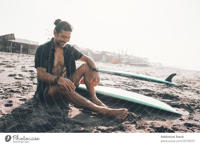 Happy ethnic man with surfboard sitting on beach happy positive rest sea enjoy sand summer young hispanic male lifestyle vacation coast ocean shore journey glad