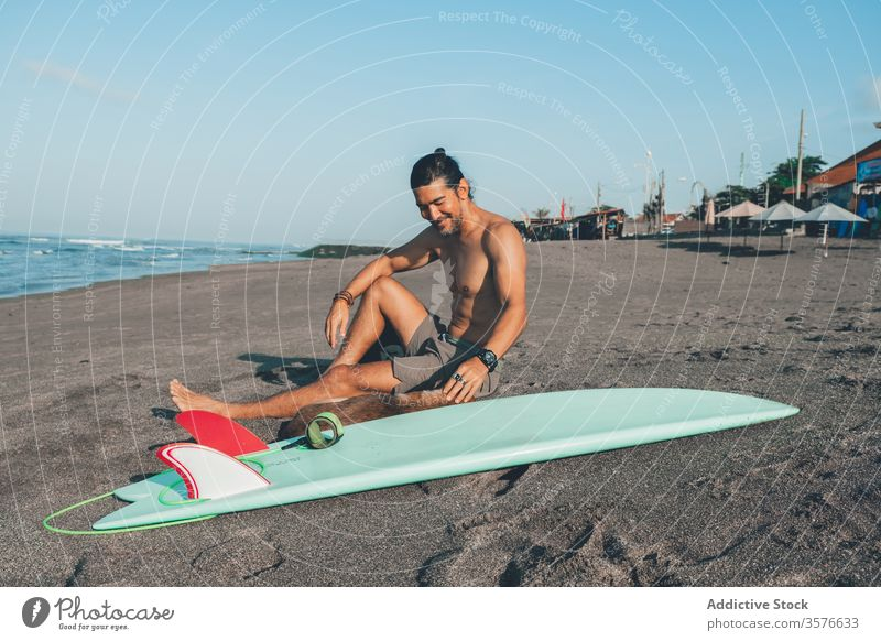 Male surfer with dog resting on beach man together pet sand sit friend surfboard companion young shirtless male summer relax coast shore lifestyle vacation