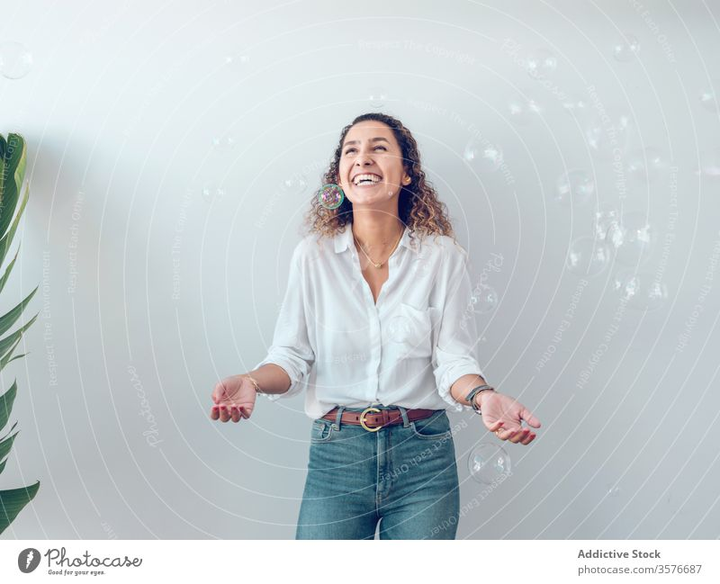 Cheerful woman catching bubbles laughing young plant leaves wall fun joy female style trendy flora decor palma de mallorca spain cheerful excited delicate