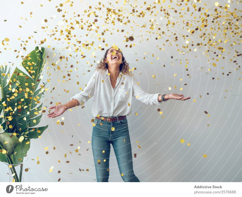 Laughing woman under falling confetti laughing party looking up wall plant young fun celebration female happy fashion joy palma de mallorca spain attractive