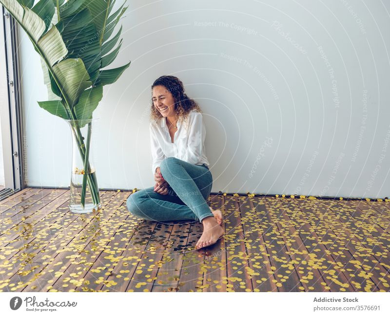 Laughing woman sitting on confetti laughing floor looking away party wall plant young fun celebration female happy barefoot fashion joy palma de mallorca spain