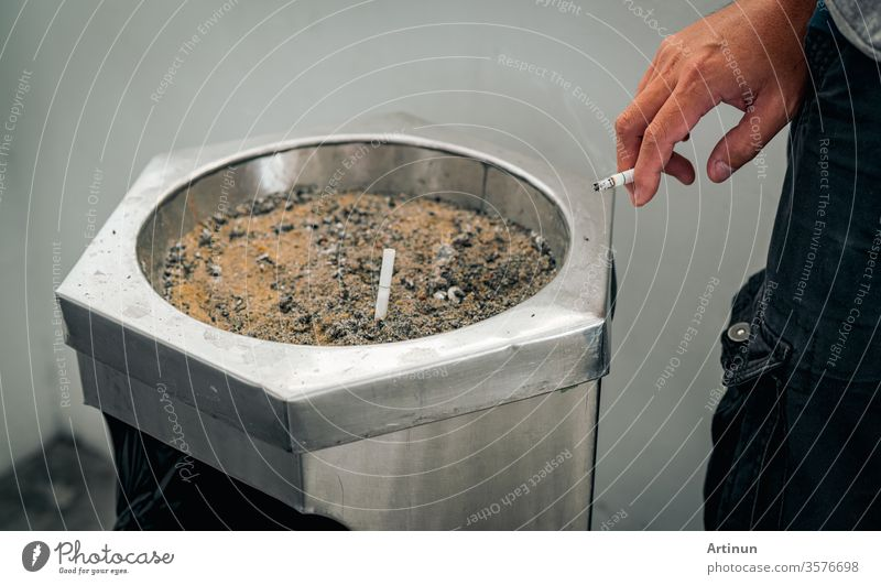Closeup hand of a man with cigarette. People smoking in smoking zone area of the mall and left cigarette in ashtray. Quit smoke or smoking cessation and lung cancer. 31 May : World no tobacco day.