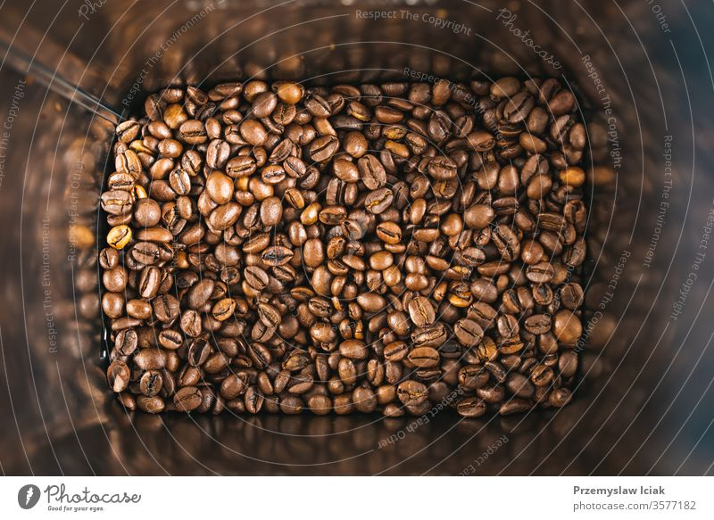 Roasted brown coffee beans inside square tin can as a background. roasted texture white black espresso dark drink natural light isolated color seed food closeup