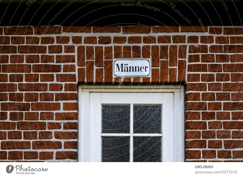 Text on an enamel sign above a door with a muntin window bears the inscription Männer men Lattice window Brick wall Facade lettering Characters Wall (barrier)