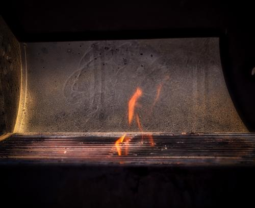 Eternal Flame. Flames that flicker out over the grill while the coal in the grill is lit and the sun casts harsh shadows Barbecue (apparatus) BBQ Coal blaze Hot