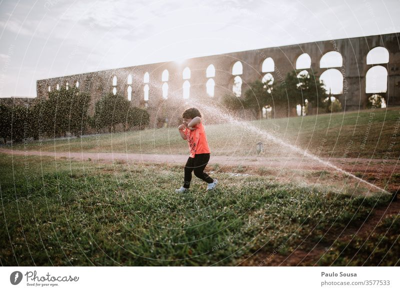 Child playing with water sprinklers Sprinkle Water Summer Summer vacation Children's game childhood Exterior shot Playing Colour photo Vacation & Travel Infancy