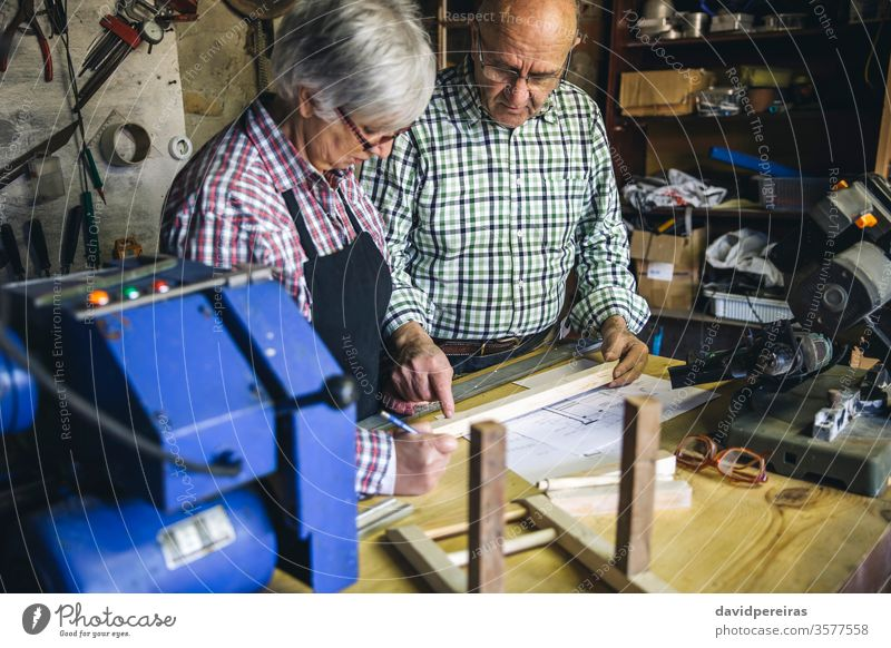 Senior couple in a carpentry senior carpenter workshop working wood mature business caucasian home retirement worker artisan cabinetmaker concentration