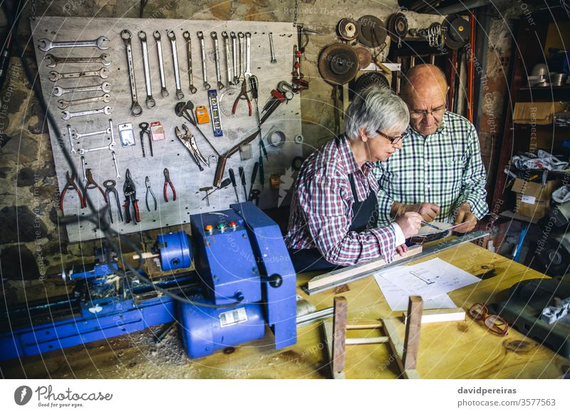 Senior couple in a carpentry carpentry shop senior working carpenter looking plans workshop wood mature machinery business caucasian home retirement worker