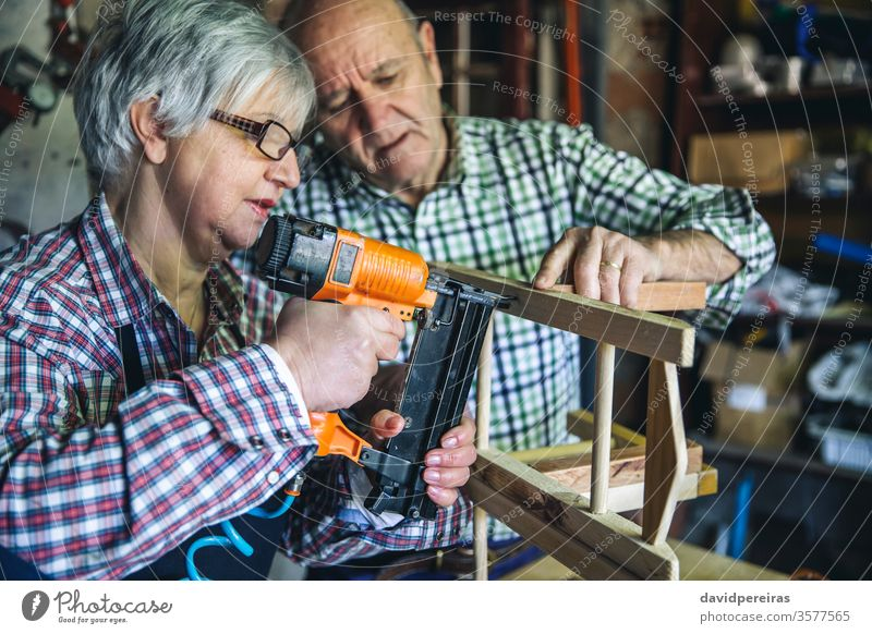 Senior couple in a carpentry woman artisan staple gun nail points assembling chair diy carpenter furniture senior workshop working wood mature business