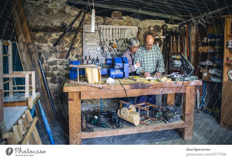 Senior couple in a carpentry workshop work bench senior measures marking working carpenter wood mature machinery business caucasian chair home retirement worker