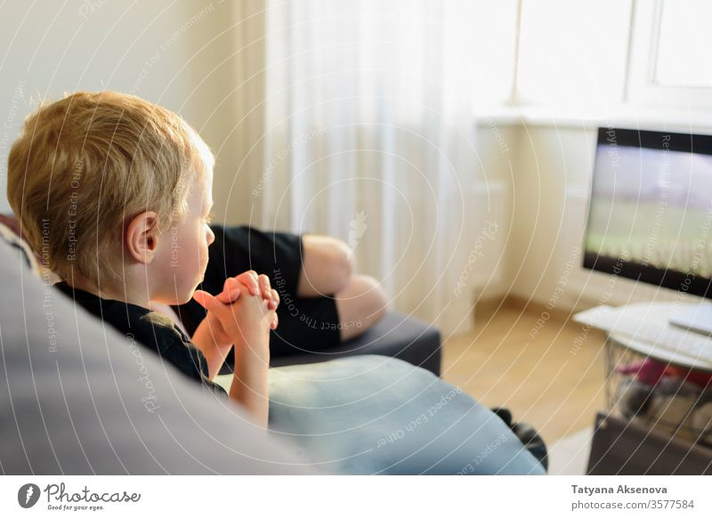Little boy watching movie on TV screen at home tv people television child sofa couch sitting family together room indoors caucasian lifestyle male technology