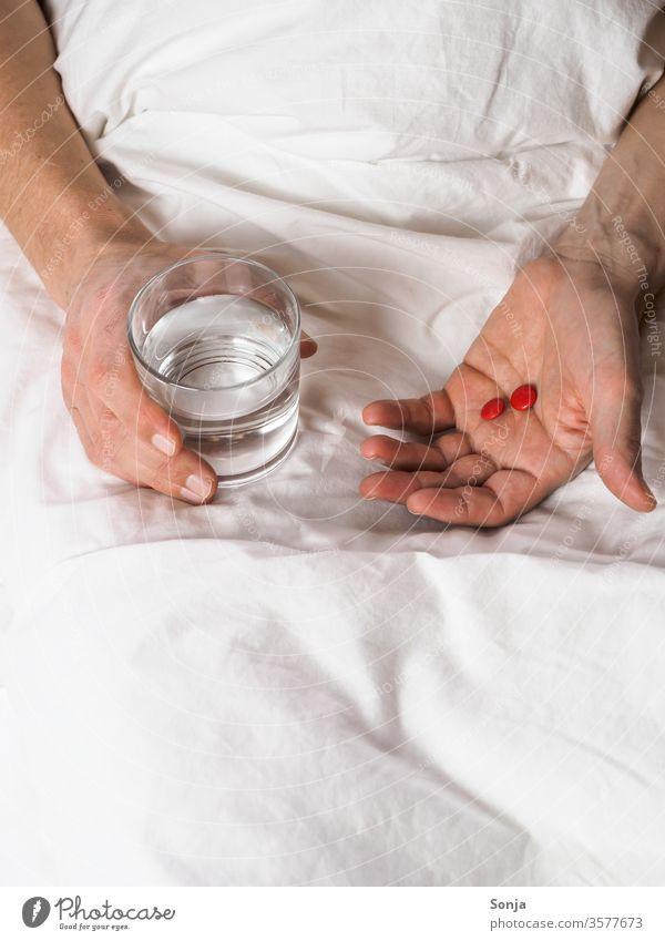 Mann hält ein Glas Wasser und Tabletten in der Hand im Bett krankheit trinkglas coronavirus stay at home Quarantine covid-19 prevention Infection Virus