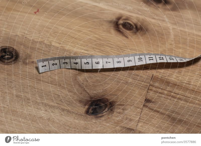 Measuring tape centimetre lies on a wooden table. Tailoring. Numbers, measure. Tape measure Centimeter figures Measure accessories Digits and numbers