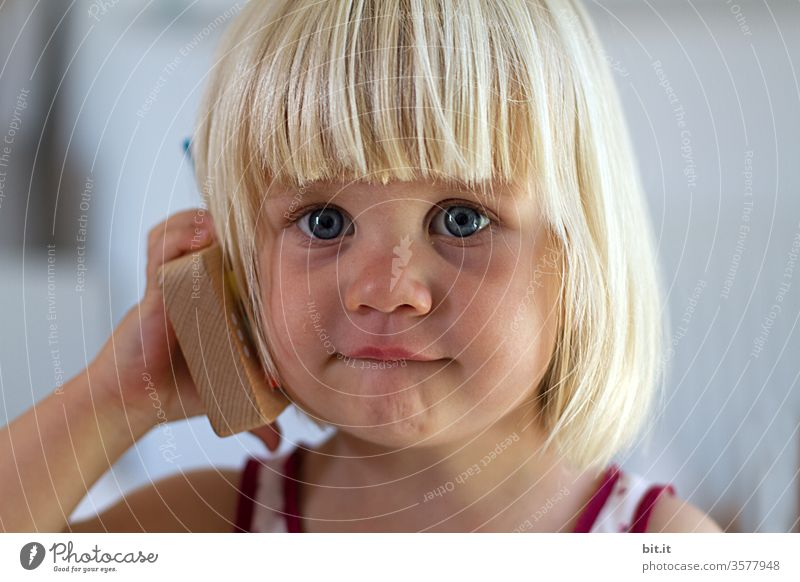 Cute, cute, blonde girl holds toy phone in hand and waits curiosity, eager for dial tone. Natural, cheerful child plays with wooden phone calling. Biological, ecological, sustainable, non-toxic children's toy.