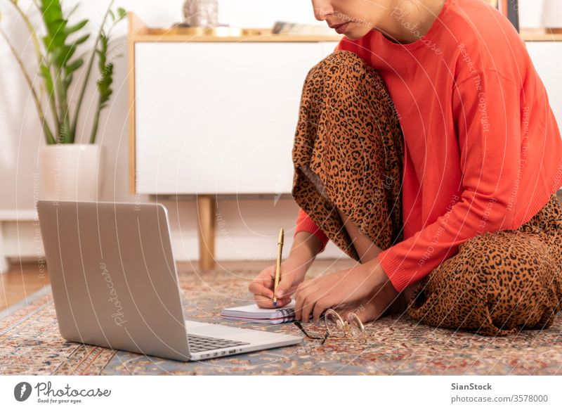 Young woman sitting on the carpet and work at her home. working studying interior beautiful portrait room looking adult internet modern communication female