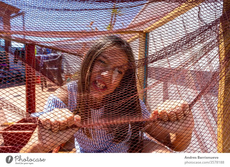 Pretty little girl dressed in a white and blue striped dress locked in a net covered cage. Isolation concept book wooden decoration planked globe child