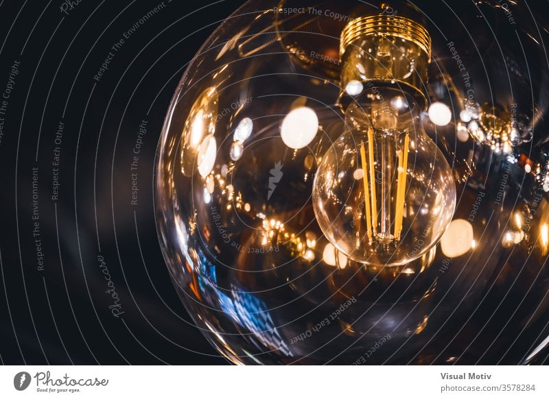 Giant vintage style light bulb lit with its retro filaments visible inside lamp glow hang giant transparent ceiling glass sphere decor illuminate design big