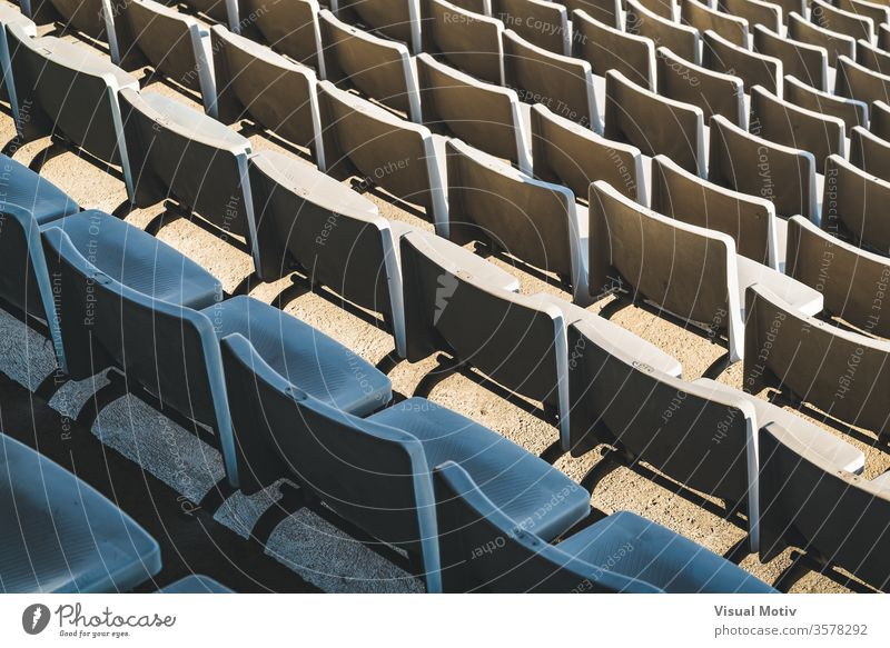 Rows of empty seats of a large outdoor stadium on a sunny day before sports event bleacher row public plastic facility chair aisle contemporary structure