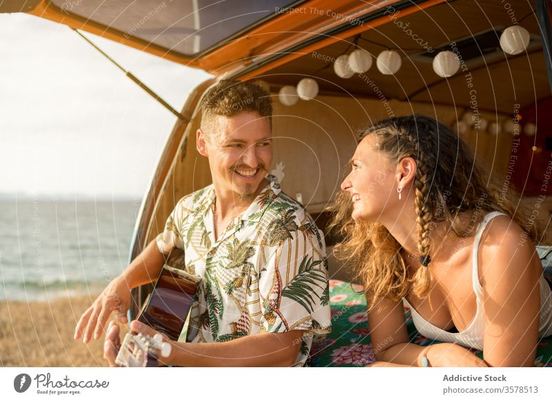 Amorous man plying on guitar in trunk of car couple musician amorous playing tender friends travel minivan having fun hippie vehicle together relationship