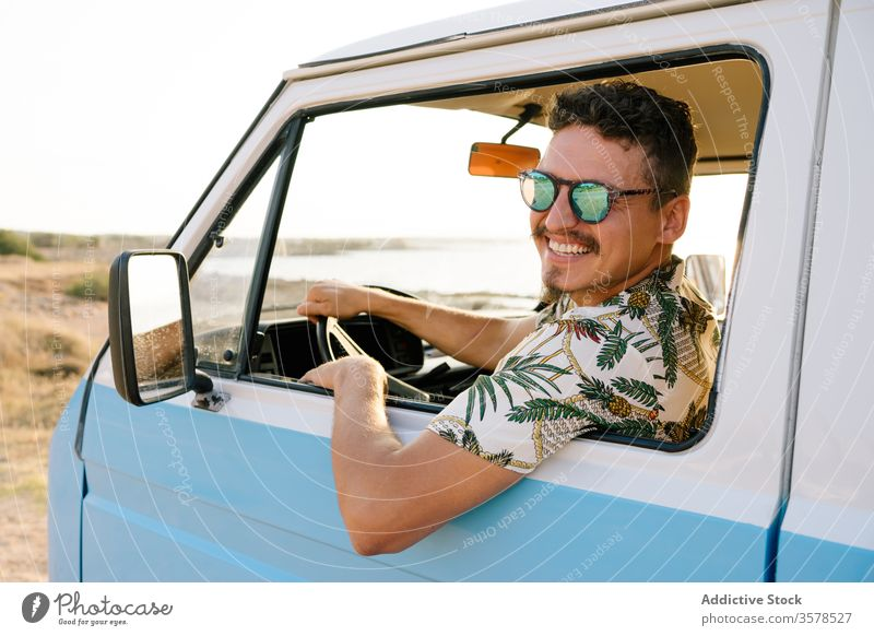Adult man sitting alone in car and dreaming on sunny shore van travel trip beach pensive contemplate parked solitude escape adventure vacation destination