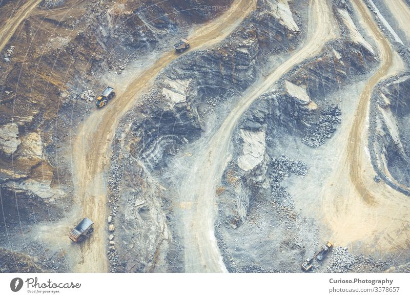 Mining from above. Industrial terraces on open pit  mineral mine. Aerial view of opencast mining. Dolomite Mine Excavation. Extractive industry. Giant excavator machinery.