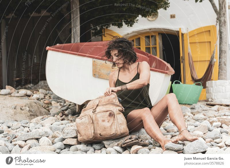 A beautiful female Latina sitting beside her bag in the seashore woman girl beauty young pretty attractive people adult white natural person travel beach