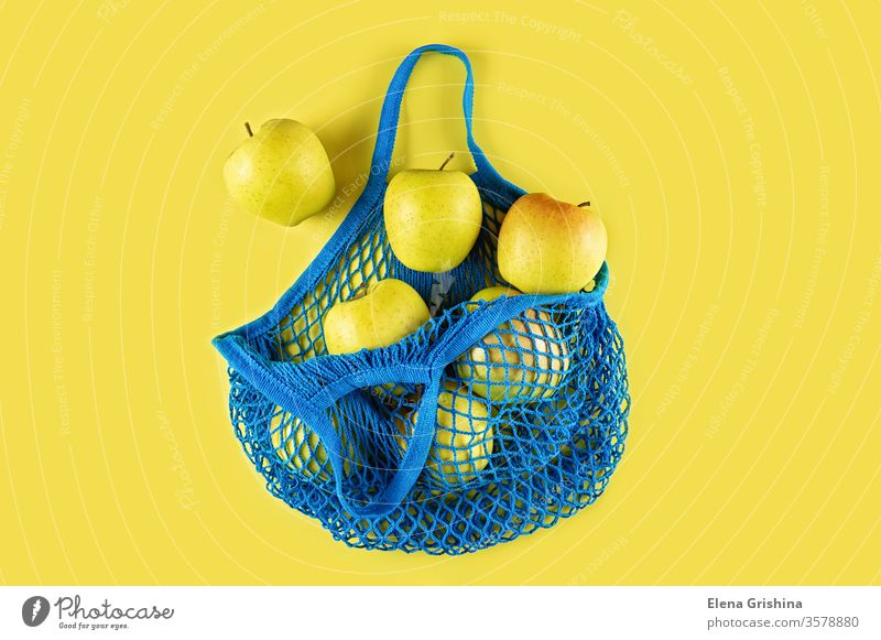 Ripe apples in a blue string bag on a yellow background. zero waste eco bag mesh bag cotton ecology concept ecological natural reusable recycle lifestyle