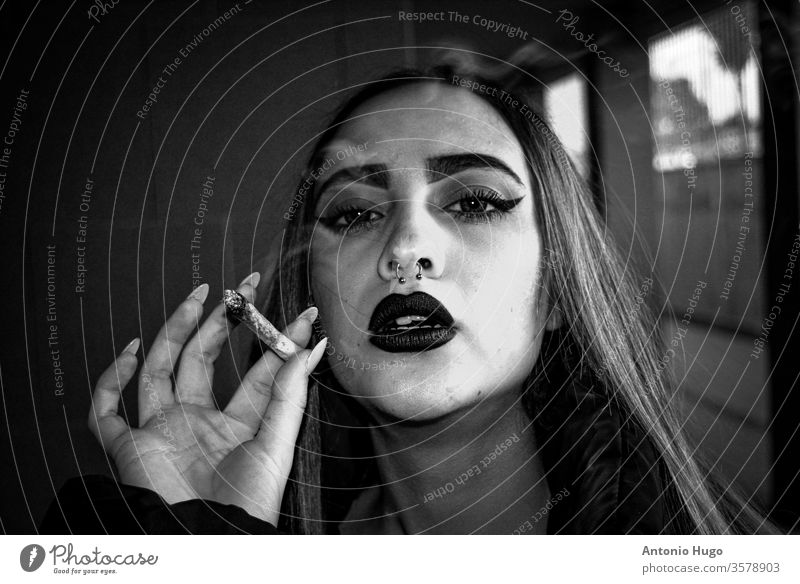 Blonde girl with red painted lips and nose piercing smoking a weed cigarette. Hipster style. Black and white. addict adult alternative attractive background
