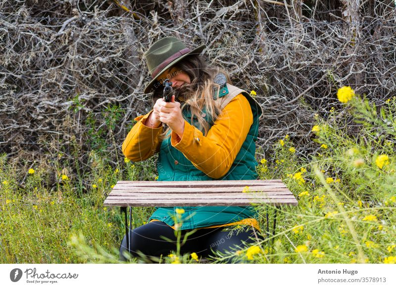 Blonde scout girl in green vest and green hat pointing rifle at camera. weapon young gun beautiful violence woman female attractive murderer kill danger fashion
