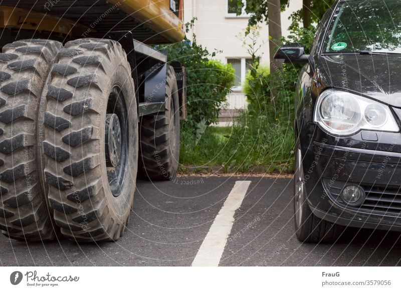 Interspaces  large and small tires Car Construction vehicle Excavator Tire Tire tread vehicles big and small Street Marker line Parked reflection half Spacing