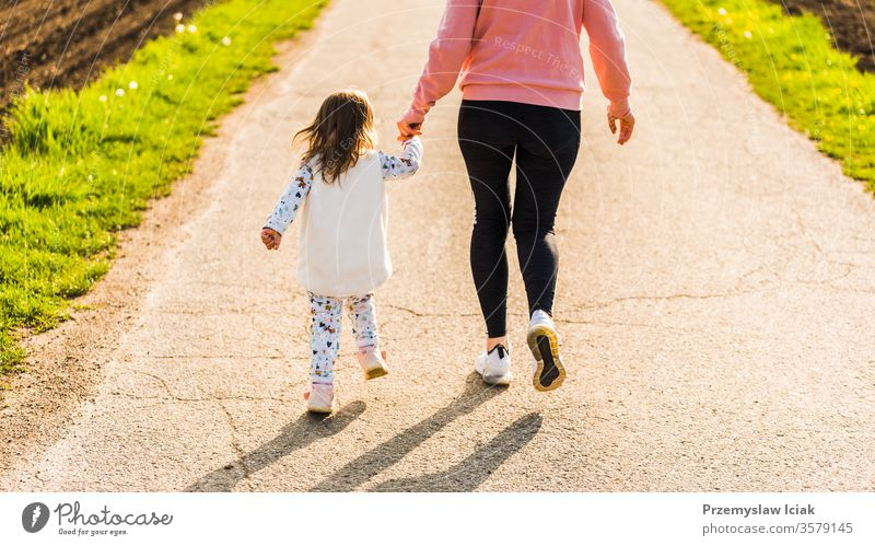 Mother and child walking on countryside road between agricultural fields towards forest in Austrian vilage durring sunset. daughter fit healthy people caucasian