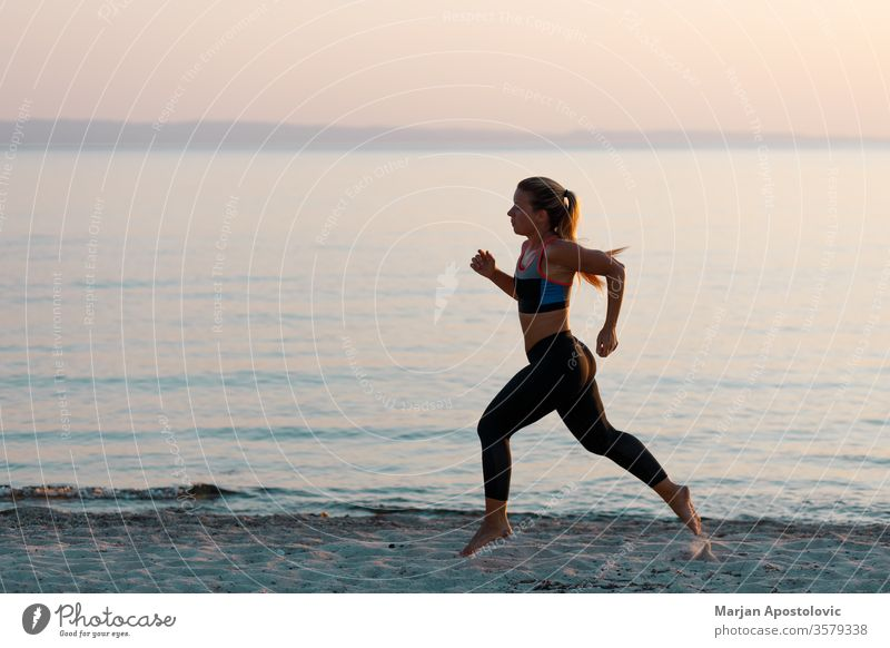 Young sporty woman running on the beach runner athletic recreation training workout healthy fit young athlete exercise lifestyle fitness active sportswear