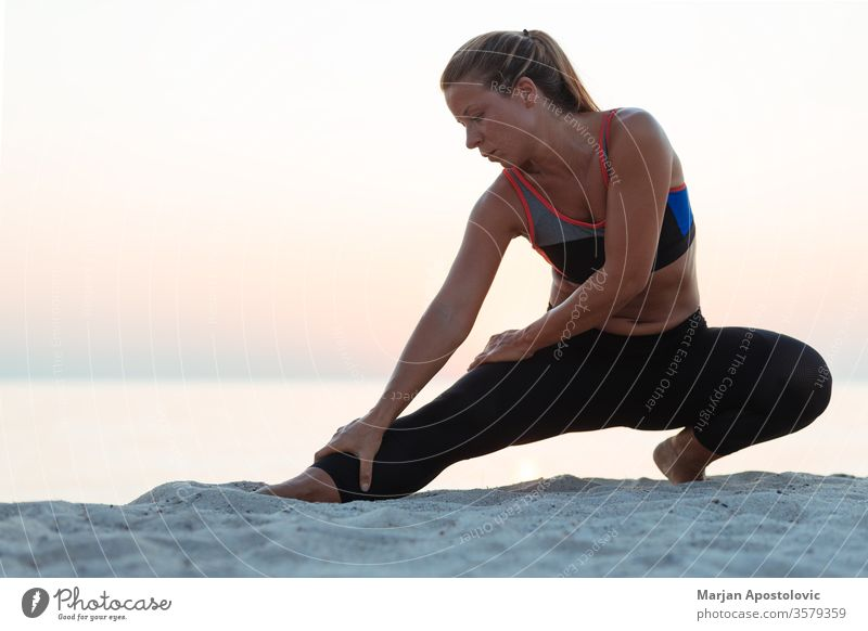 Young sporty woman stretching on the beach runner running athletic recreation training workout healthy fit young athlete exercise lifestyle fitness active