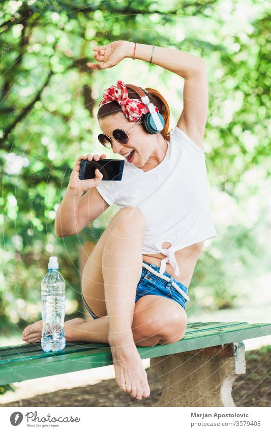 Young woman listening to the music on her smartphone in the park young happy wifi lifestyle enjoying fun joyful singing springtime summer cute beautiful modern