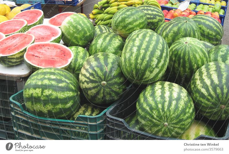 Watermelons in baskets at a Mediterranean market stall. In the background bananas and apples Melon fruits Nutrition Summer Food Delicious Juicy Bananas Round