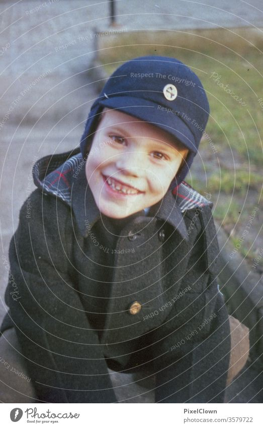 A little boy in a cap laughs into the camera Boy (child) Child Playing Face Infancy Happiness Joy Human being Laughter Retro children
